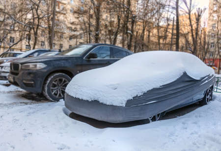 Real car in gray case under snow in winter day Stock Photo