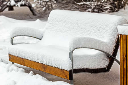 Real pretty wooden bench completely covered in snow at day Stock Photo