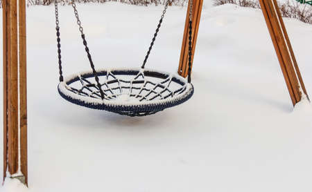 Real empty children's round swing in yard on winter day in big snow Stock Photo