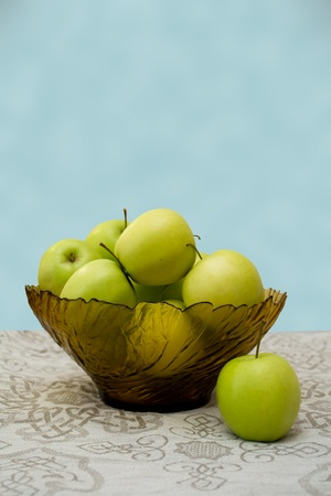 green apples in a glass vase on the table cloth photo