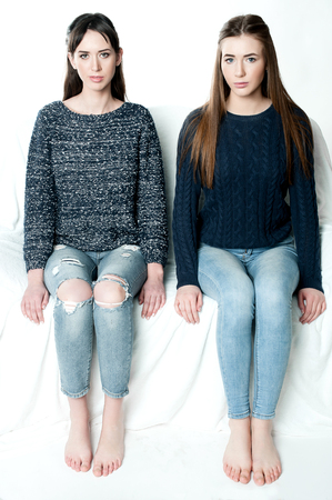 15 20: Young and beautiful sisters in friendship, sharing joy, trust, love, happiness and support, hugs, laughs and smiles wearing jeans Stock Photo