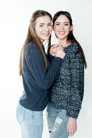 standing together: Young and beautiful sisters in friendship, sharing joy, trust, love, happiness and support, hugs, laughs and smiles wearing jeans Stock Photo