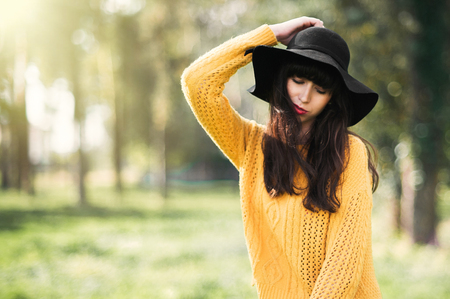 Retrato de un Brunnete feliz y sonriente niña en un sombrero negro y un suéter amarillo