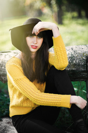 Portrait of a brunnete happy and smiling girl in a black hat and yellow sweater
