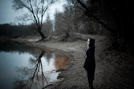 Colpo di una donna gotica in una foresta. Moda.