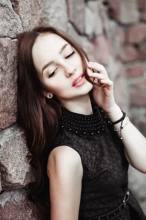 celos: beautiful sad young woman on a stone wall background posing in a black dress, very sensual and emotional