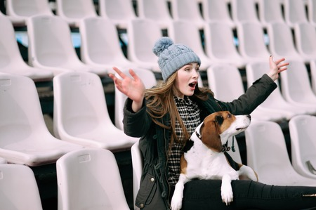 stroll: Young hipster girl with her pet estonian hound dog playing and having fun outdoor in the park. Fans at the stadium