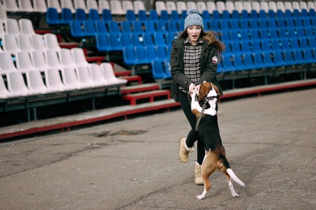 stroll: Young hipster girl with her pet estonian hound dog playing and having fun outdoor in the park.