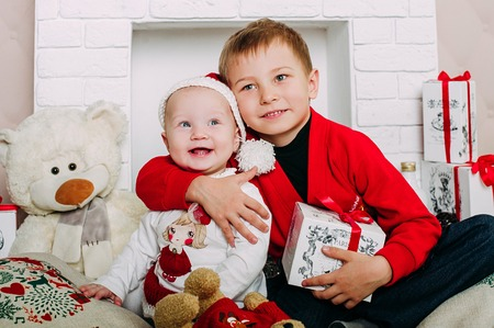 twee: Portrait of happy children with Christmas gift boxes and decorations. Two kids having fun at home