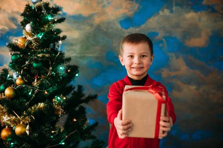 christmastide: Portrait of adorable boy with giftboxes