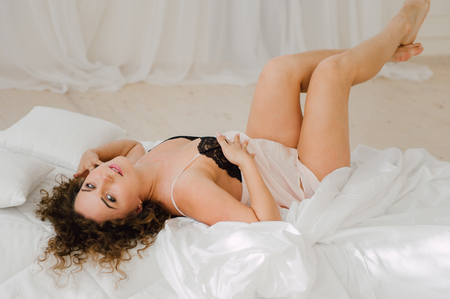 awaken: Sexy woman in bed in the morning showing her beautiful body. She doesnt wants to wake up. Awaken with natural light in her bedroom and covered with the bed sheets. Stock Photo