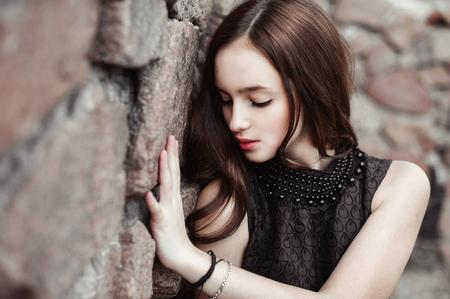 celos: hermosa mujer joven triste en una pared de piedra de fondo posando en un vestido negro, muy sensual y emocional