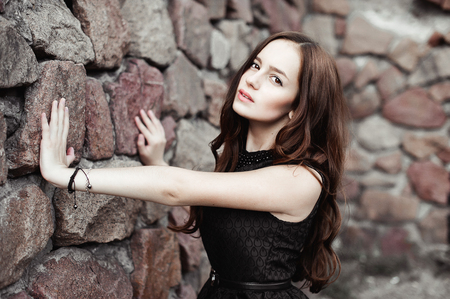 beautiful sad young woman on a stone wall background posing in a black dress, very sensual and emotional