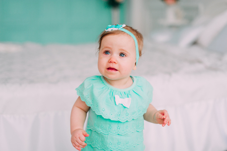 Adorable little baby girl laughing, smiling, creeping & playing in the studio wearing mint dress Stock Photo
