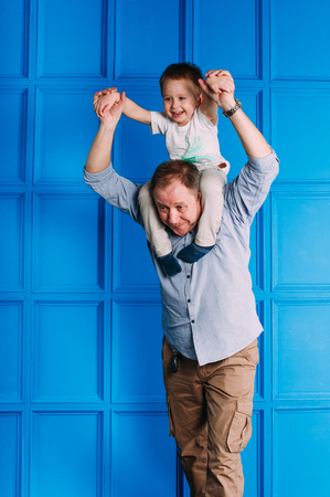 Laughing grandfather with his grandson as they play together indoors in the living room with the cute young boy hugging him from behind Stock Photo