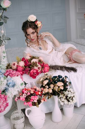 Beautiful young woman, hair decorated with flowers. Perfect makeup. Beauty fashion. Eyelashes. Studio retouched shot. Tender and sweet atmosphere, pastel colors Stock Photo
