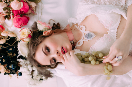 visage: Beautiful young woman, hair decorated with flowers. Perfect makeup. Beauty fashion. Eyelashes. Studio retouched shot. Tender and sweet atmosphere, pastel colors Stock Photo