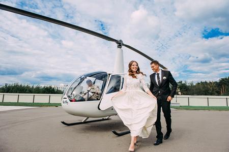 Gelukkige mooie jonggehuwden dichtbij de helikopter Stockfoto