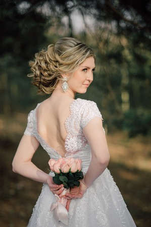 Back of beautiful bride with bridal bunch Stock Photo