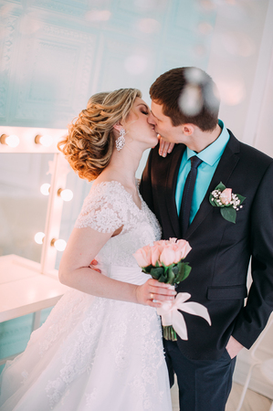 Happy couple. Wedding photo shoot in the white studio with wedding decor kisses, hugs. On the background of make up mirror Stock Photo