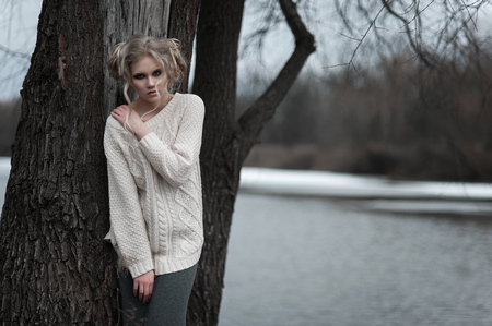 smoky eyes: Close up of beautiful young  blonde woman with blue eyes in white pullover.  Winter, spring, outdoor portrait. Professional beauty make-up: dark smoky eyes and pale lips and hair style. Stock Photo