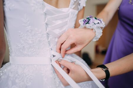 bridesmaid tying bow on wedding dress Stock Photo