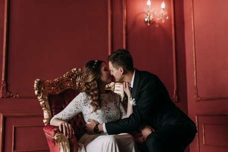 cute wedding couple in the interior of a classic studio decorated. hey kiss and hug each other Reklamní fotografie