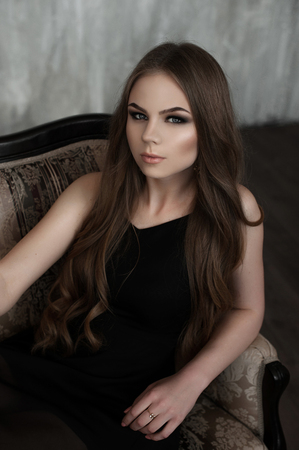 Young girl with long beautiful hair and smoky eyes wearing black maxi evening dress sitting on a classic style sofa. Studio shot