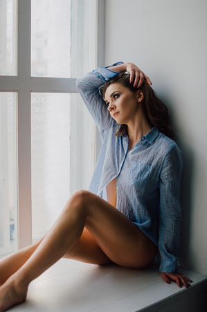 retouched: Young pretty woman sitting at window and looking outside enjoys of rest, wearing blue shirt. Studio retouched shot. Stock Photo