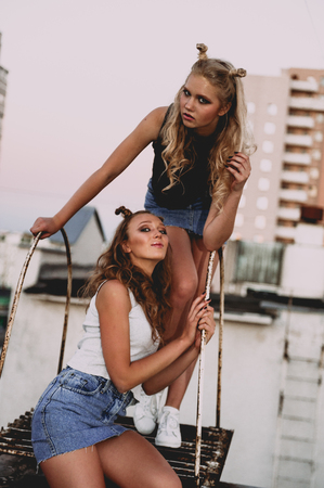 messed: lifestyle and people concept: Fashion portrait of two stylish girls best friends wearing jeans skirts, outdoors. Happy summer time for fun. Concept of 90s