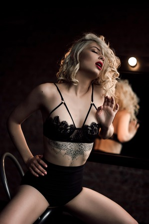 Beautiful fashion model sexy and passhionate blonde woman with red lips posing near the mirror wearing black sexy lingerie