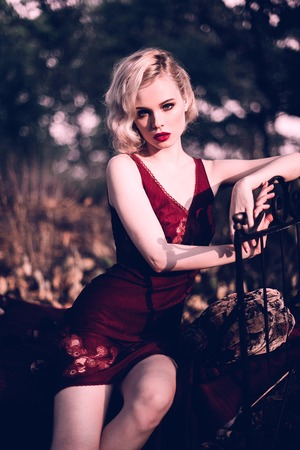 amp: Beautiful and elegant blonde woman with red lips and hair waves wearing wine red nightie posing on the bed outdoors, retro vintage style and fashion