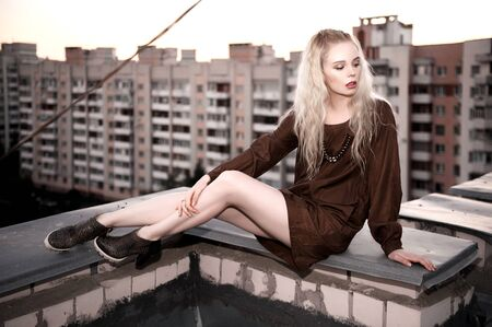 Outdoor portrait of young beautiful happy lady posing on street. Model wearing stylish clothes. Girl looking down. Female fashion. City lifestyle. Copy space.