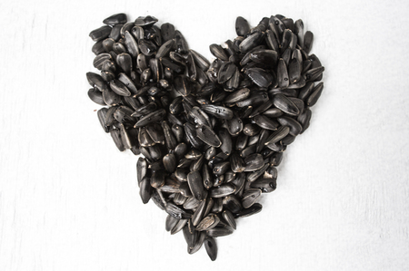 sunflower seeds: Black sunflower bird seed forms a heart shape on white background.