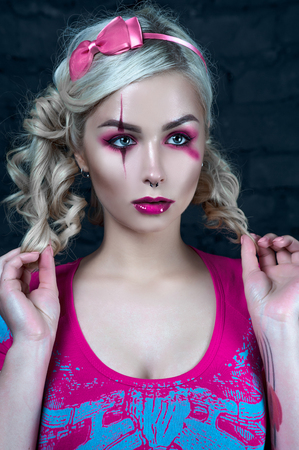 Beautiful blonde girl with two pigtails, with creative make-up: pink glossy lips, wearing pink skeleton dress. for the Halloween party. Close up Stock Photo
