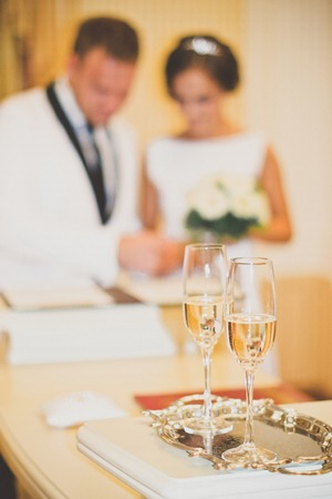 heartwarming: Wedding glasses are in the foreground. Blurred outlines newlyweds seen in the background. Stock Photo