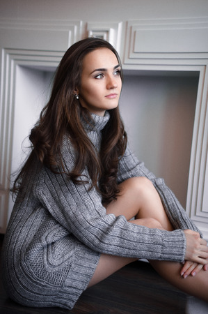 Young beautiful brunette woman  wearing knitted cardigan sitting relaxing by the window. Home chill out concept.