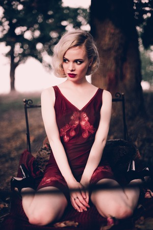 Beautiful and elegant blonde woman with red lips and hair waves wearing wine red nightie posing on the bed outdoors, retro vintage style and fashion