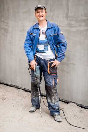 Young construction worker outdoors. Renovation background.