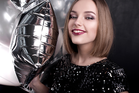 Close up fashion portrait of a young beautiful elegant girl with bright party make up in evening black sequin top. She is keeping silver stars balloons in her hand. Girl at the party.