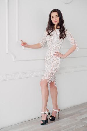 the magnificent: fashion portrait of a young beautiful woman in a lace elegant white dress posing in a studio, positive and happy