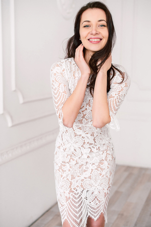 fashion portrait of a young beautiful woman in a lace elegant white dress posing in a studio, positive and happy