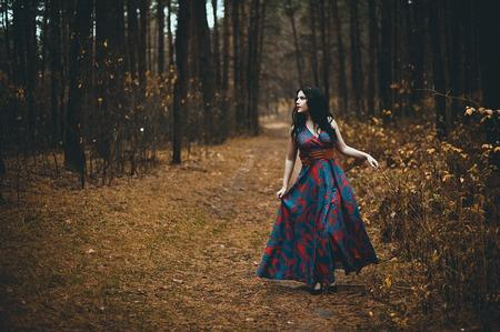 Red Hooded Woman Holding Apple Fairytale Portrait - Fairytale afbeelding van een mooi meisje draagt een rode kap in de buurt van het bos Stockfoto