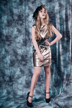 Attractive young woman posing in sequin dress. Studio image