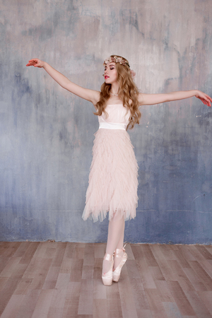 highkey: Beautiful legs of young ballerina who puts on pointe shoes at white wooden floor background, top view from above with copy space. Ballet practice. Beautiful slim graceful feet of ballet dancer.