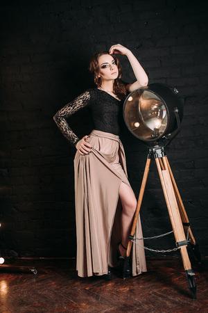 個性。暗い背景上のミラー近く黒パーティー ドレスに立っての思いやりのあるエレガントな女性。補正後のファッション撮影 写真素材