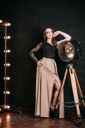 retouched: Individuality. Thoughtful Elegant Lady in Black Prom Dress standing near mirror on dark background. fashion retouched shot Stock Photo