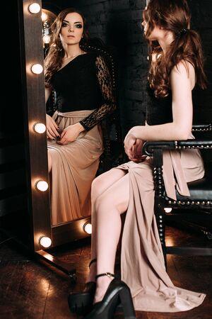 Individualité. Une Dame élégante réfléchie dans une robe de bal noir debout près d'un miroir sur fond sombre. tir retouché à la mode