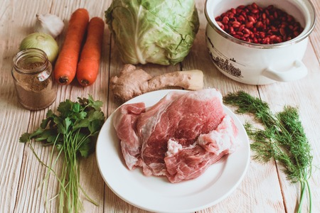 gua: Food ingridients: red beans, carrot, cabbage, meat, onion, ginger for recipe stewed beans with meat on wooden background. Steps in cooking, process of preparing food. Concept of homemade healthy food. Flatlay, top view