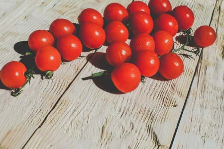 Cherry tomatoes on wooden table background with copy space, flat lay